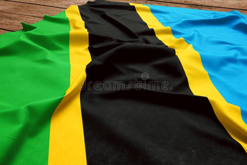 Flag of Tanzania on a wooden desk background. Silk Tanzanian flag top view.  stock images