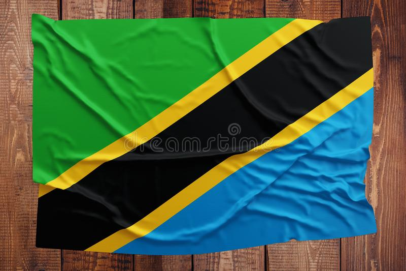 Flag of Tanzania on a wooden table background. Wrinkled Tanzanian flag top view.  stock photos