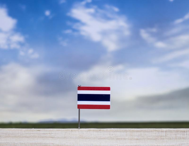 Flag of Thailand with vast meadow and blue sky behind it. royalty free stock image