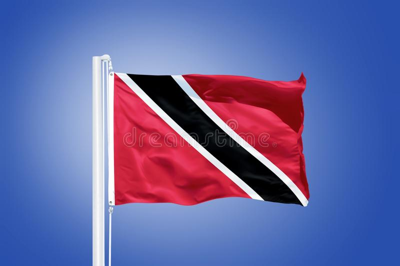 Flag of Trinidad and Tobago flying against a blue sky.  royalty free stock photography