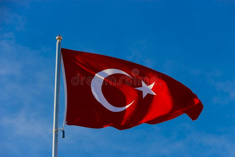 Flag of Turkey on flagpole waving in the wind against the blue sky royalty free stock images