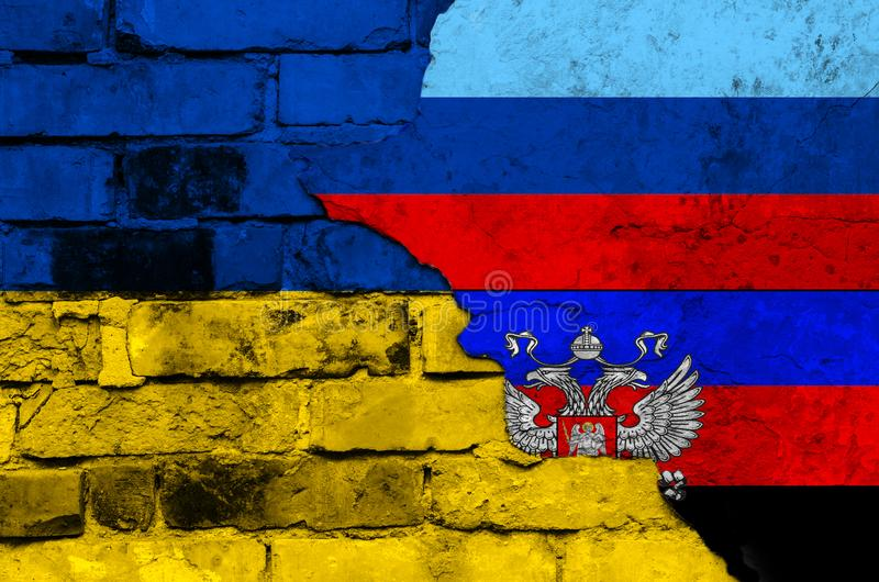 Flag of Ukraine and Donetsk and Lugansk People`s Republic on a textured brick wall. Horizontal frame stock image