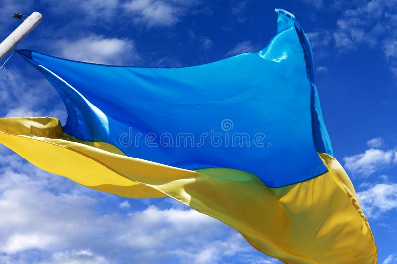Flag of Ukraine waving in wind on blue sky with clouds royalty free stock photography