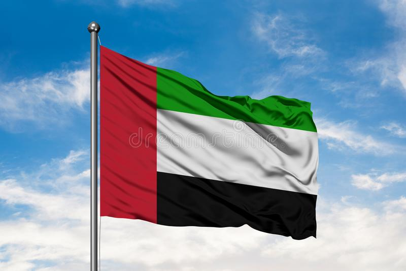 Flag of United Arab Emirates waving in the wind against white cloudy blue sky. UAE flag.  royalty free stock image