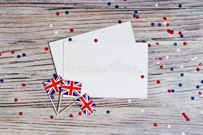 Flag of United Kingdom of Great Britain in hand on white wooden background top view. copy space. the concept of independence day, stock photography