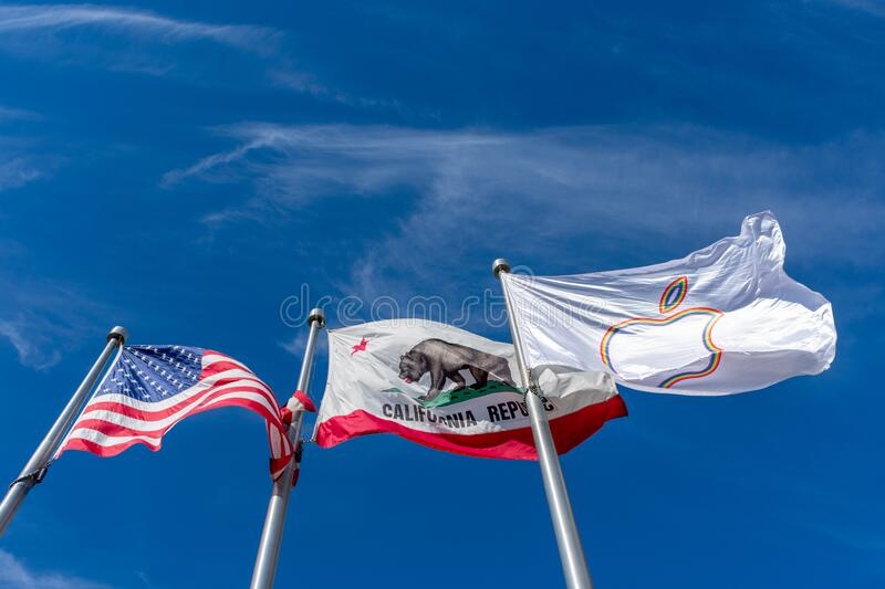 Flag of the United States, Flag of California and Apple Pride Flag. Flying waving in the wind under blue skies - Cupertino, California, USA - June 27, 2019 royalty free stock images