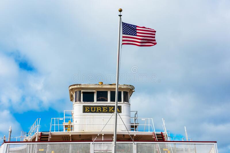 Flag of the United States flying waving beautifully in wind above bridge deck of Eureka ferry boat preserved at San Francisco. Maritime National Historical Park royalty free stock image