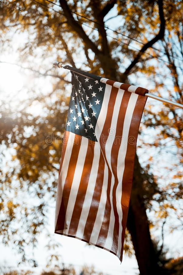 Flag of the united states in a vertical shot with a blurred background. A flag of the united states in a vertical shot with a blurred background royalty free stock photography