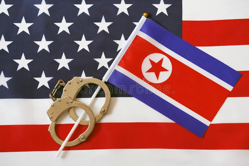 Flag of USA and North Korea. Handcuffs. Sanctions. North Korea flag in handcuffs on the background of the American flag. US sanctions against North Korea stock image
