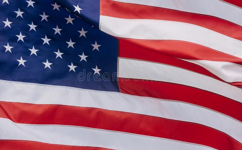 Flag of the USA with sunflare. Waving in the wind, america, american, symbol, patriotic, national, freedom, patriotism, closeup, red, united, blue, independence royalty free stock images