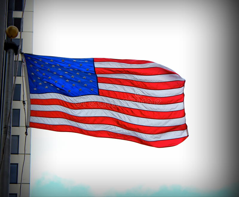 Flag USA. Flag of USA unfurled against a white cloud on a blue sky stock photography