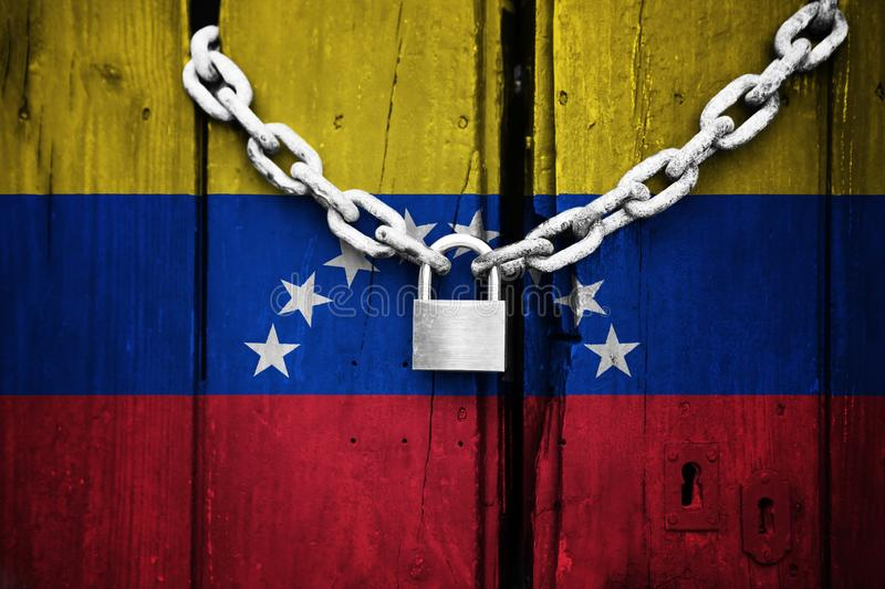 Flag of Venezuela painted on an old and cracked wooden door, which is closed by an old chain and a padlock that conceptually repre. Sents the lack of freedom in royalty free illustration