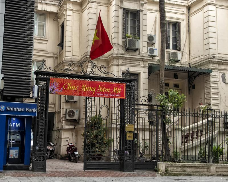 Flag of Vietnam over a banner celebrating Tet 2019 at the entrance to a middle school in Hanoi, Vietnam stock photography