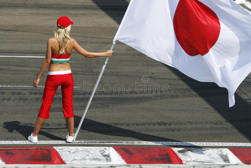Flag Woman. Young blonde woman presenting the japan flag for a racing driver stock photography