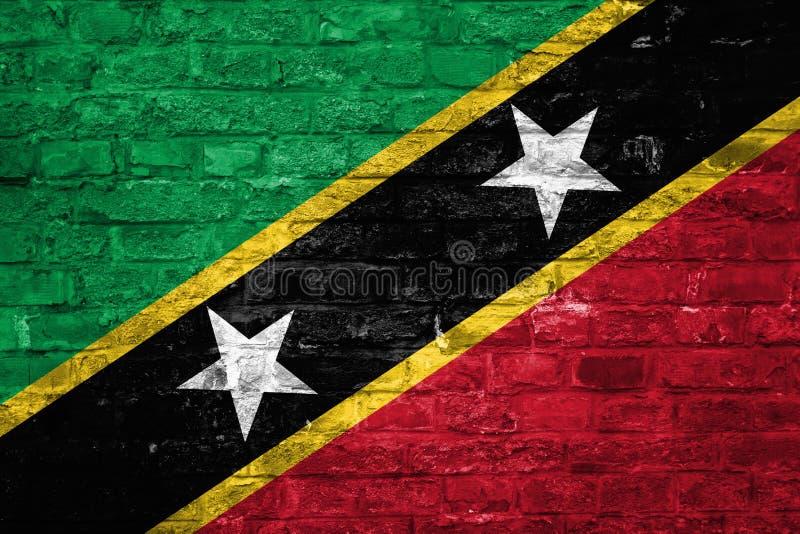 Flaga Świątobliwy Kitts i Nevis nad starym ściany z cegieł tłem, powierzchnia obraz royalty free