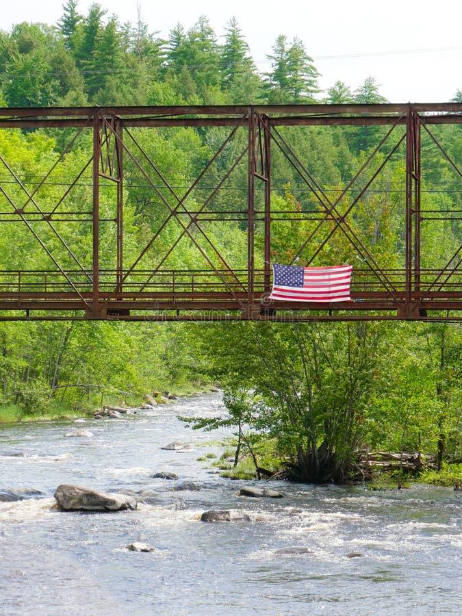 Flaga Amerykańska lata nad starym pociągu mostem zdjęcia royalty free
