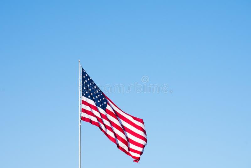 Flaga Amerykańska Przeciw Bezchmurnemu niebu Unfurled w wiatrze obraz stock