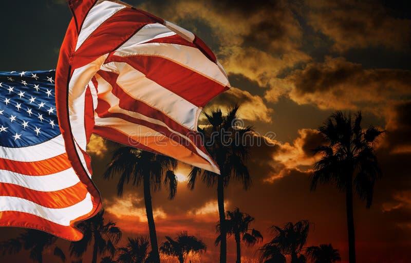 Flaga amerykańska przy sylwetek drzewkami palmowymi na zmierzchu zdjęcia stock
