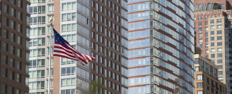 Flaga amerykańska z drapacz chmur w tle na Manhattan wyspie w Miasto Nowy Jork fotografia stock