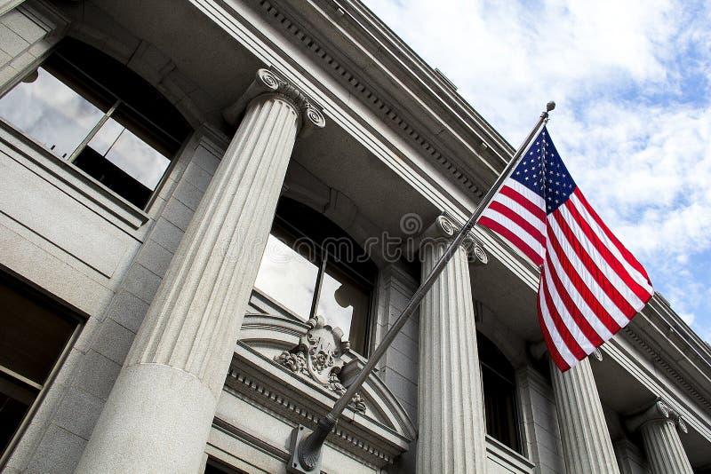Flaga Amerykańskiej dmuchanie w wiatrze przed kamiennym szpaltowym budynkiem z niebieskim niebem i chmurami zdjęcia stock