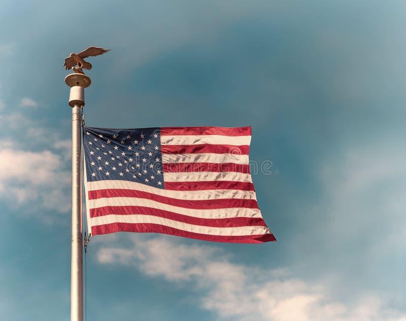 Flaga amerykańskiej falowanie w wiatrze przeciw niebieskiemu niebu zdjęcia stock
