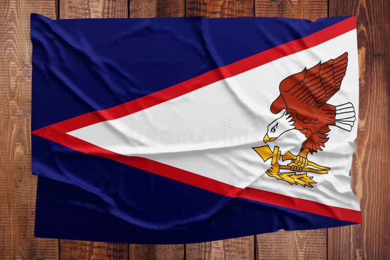 Flaga amerykanin Samoa na drewnianym sto?owym tle Marszcz?cy Samoa?ski chor?gwiany odg?rny widok zdjęcia stock