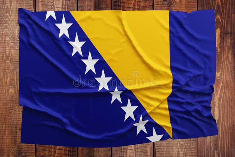 Flaga Bo?nia, Herzegovina na drewnianym sto?owym tle - Marszcz?cy bo?niak flagi odg?rny widok zdjęcie royalty free
