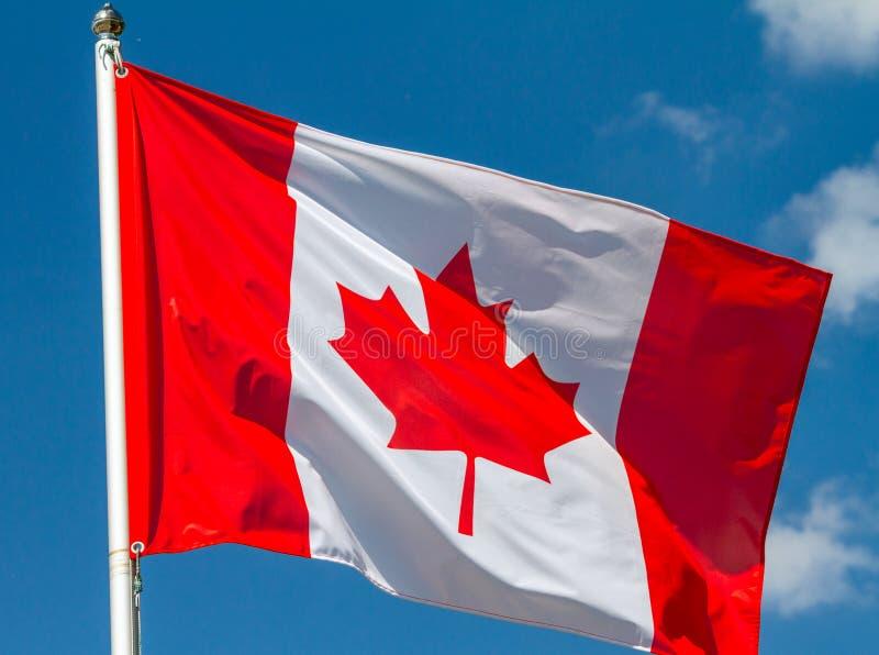 Flaga Kanada falowanie w wiatrze na flagpole przeciw niebu z chmurami na słonecznym dniu zdjęcia stock