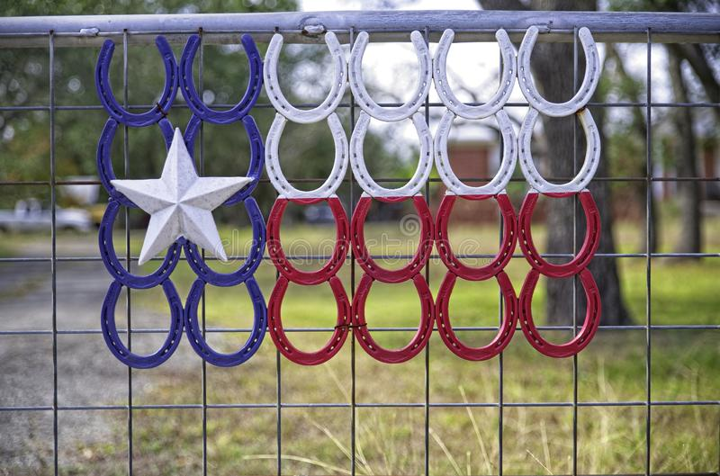 Flaga Lone Star Texas stworzona z czerwonych, białych i niebieskich koni na płocie z bramą fotografia stock