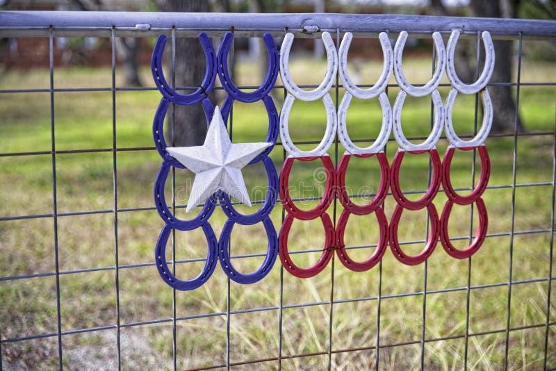 Flaga Lone Star Texas stworzona z czerwonych, białych i niebieskich koni na płocie z bramą obraz royalty free