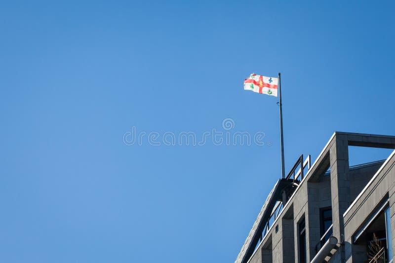 Flaga Montreal z swój ikonowym żakietem ręki rezygnuje w powietrzu na urząd miasta miasto obraz stock