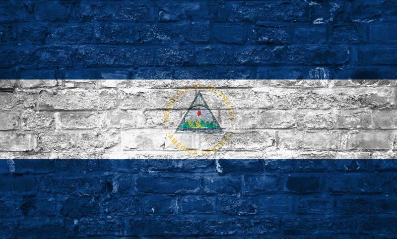 Flaga Nikaragua nad starym ściany z cegieł tłem, powierzchnia zdjęcie stock