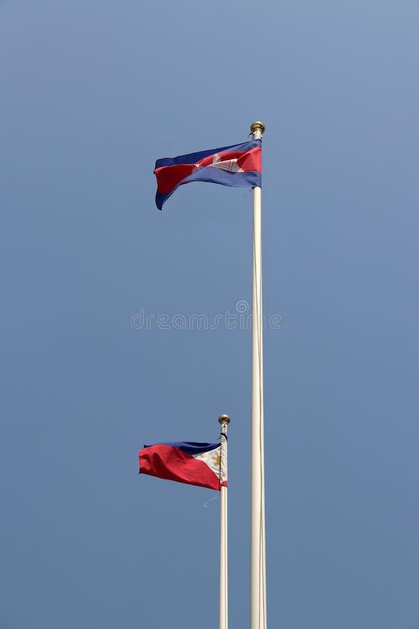 Flaga państowowa Kambodża i Filipiny na jaskrawym niebieskiego nieba tle Wystrzelony wiatrem daleko od fotografia royalty free