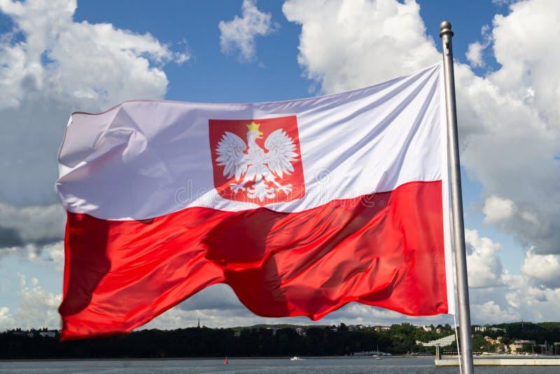 flaga Poland Polska flaga państowowa z emblematem na chmurnym niebieskim niebie fotografia royalty free