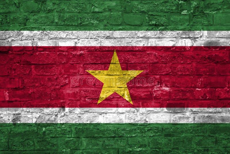 Flaga Suriname nad starym ściany z cegieł tłem, powierzchnia fotografia stock