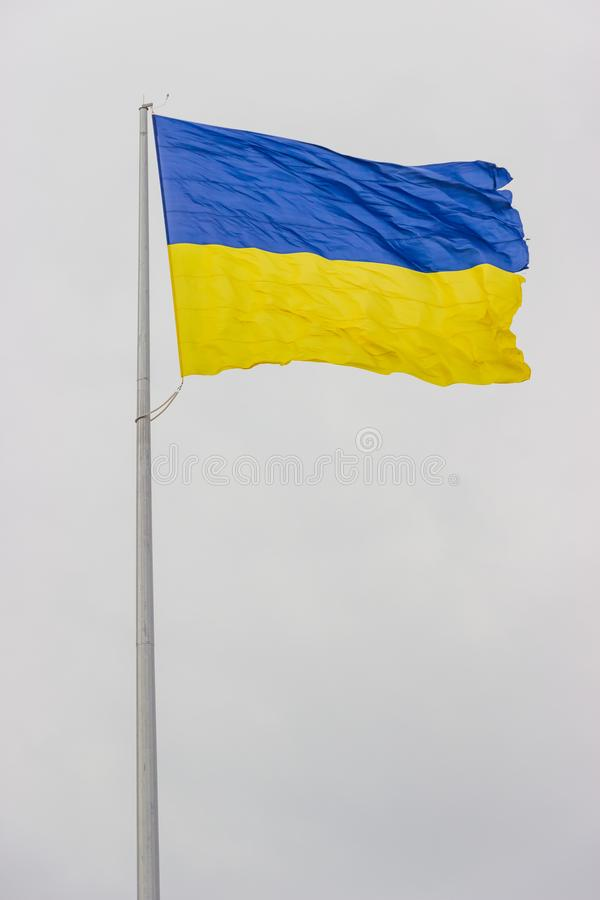 Flaga Ukraina trzepocze w wiatrze na wysokim flagpole w Dnipro mieście Strzelać przy zamkniętym pasmem Real flaga w wietrznym pop obraz royalty free
