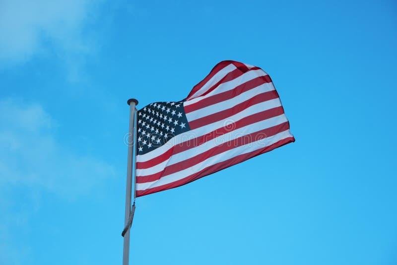 Flaga usa falowanie w wiatrze na niebieskiego nieba tle zdjęcia royalty free
