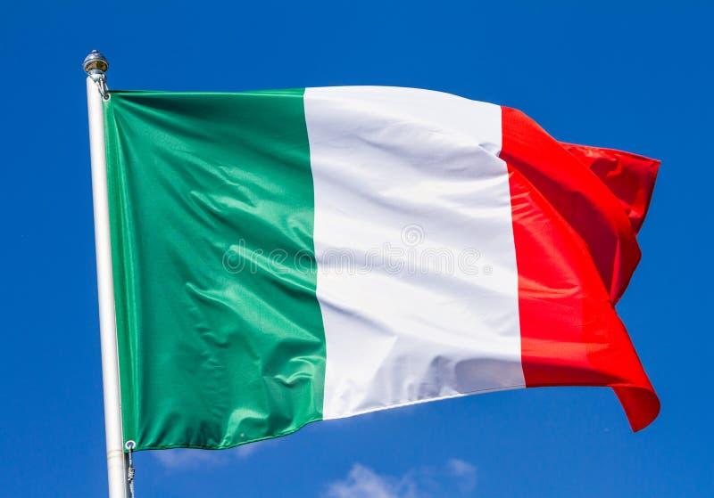 Flaga Włochy falowanie w wiatrze na flagpole przeciw niebu z chmurami na słonecznym dniu zdjęcie royalty free
