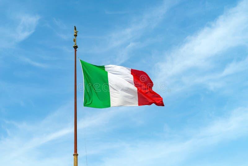 Flaga Włochy na flagpole trzepocze w wiatrze przeciw niebieskiemu niebu fotografia stock