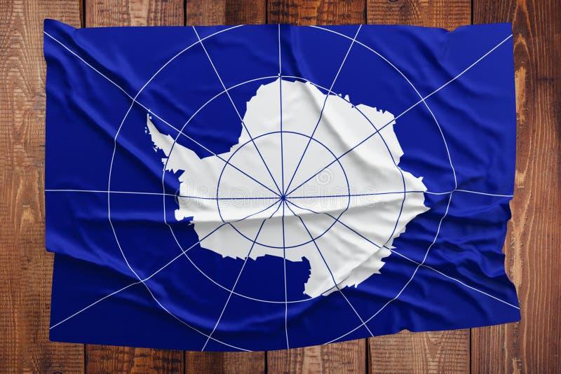 Flagga av Antarktis p? en tr?tabellbakgrund B?sta sikt f?r rynkig flagga arkivfoto