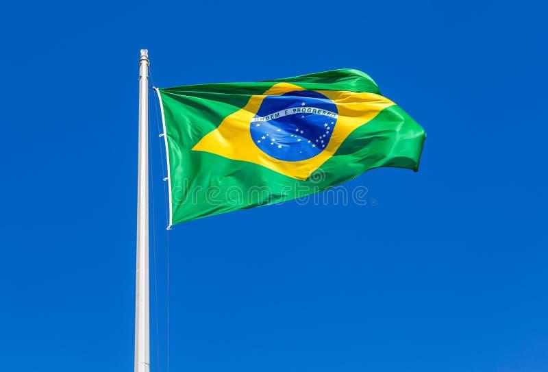 Flagga av Brasilien som vinkar i vinden mot himlen royaltyfri bild