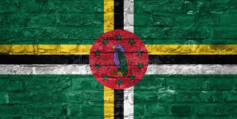 Flagga av Dominica över en gammal bakgrund för tegelstenvägg, yttersida royaltyfria bilder