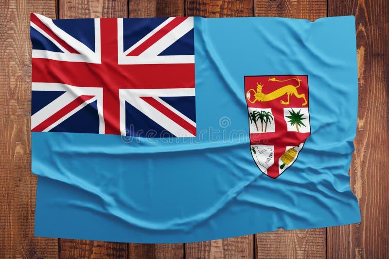 Flagga av Fiji p? en tr?tabellbakgrund B?sta sikt f?r rynkig Fijian flagga royaltyfri foto