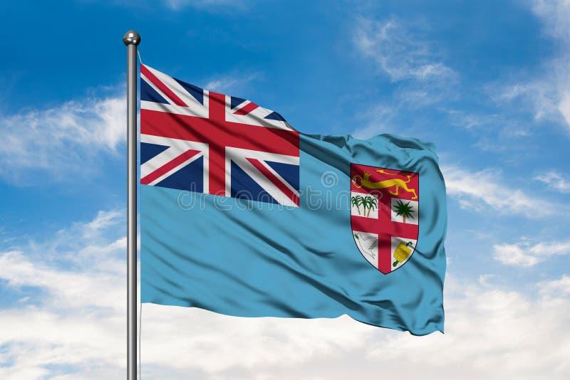 Flagga av Fiji som vinkar i vinden mot vit molnig blå himmel Fijian flagga royaltyfri foto