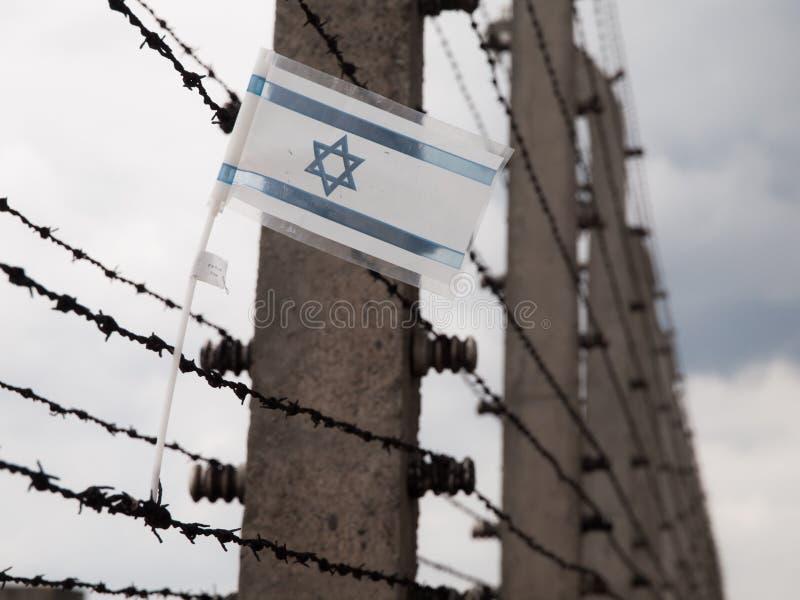 Flagga av Israel i staketet av koncentrationsläger royaltyfri foto