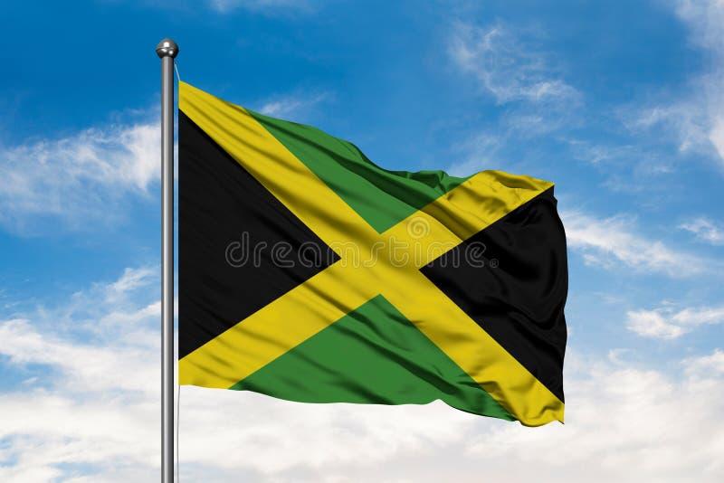 Flagga av Jamaica som vinkar i vinden mot vit molnig blå himmel flag jamaican royaltyfri foto
