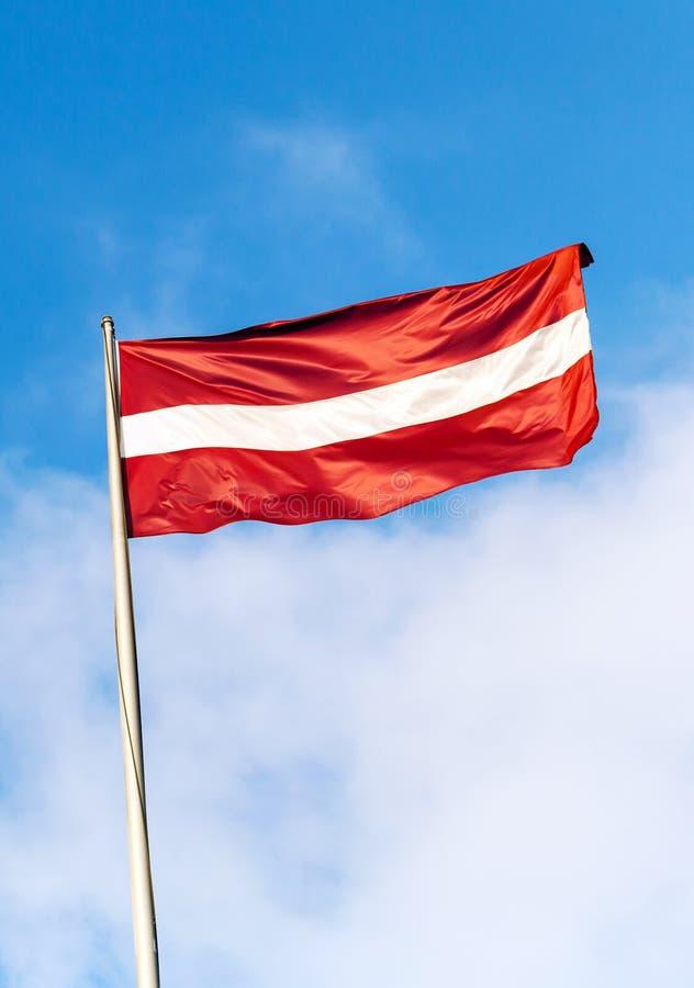 Flagga av Lettland ovannämnd blå himmel arkivfoto