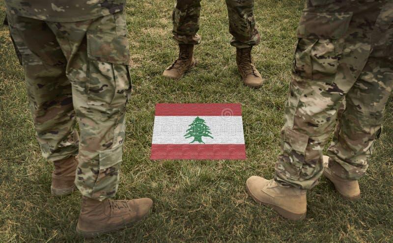 Flagga av Libanon och soldatben på gräscollaget arkivfoto