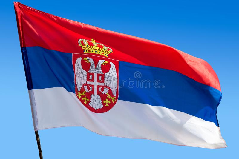 Flagga av republiken av Serbien mot blå himmel arkivbild
