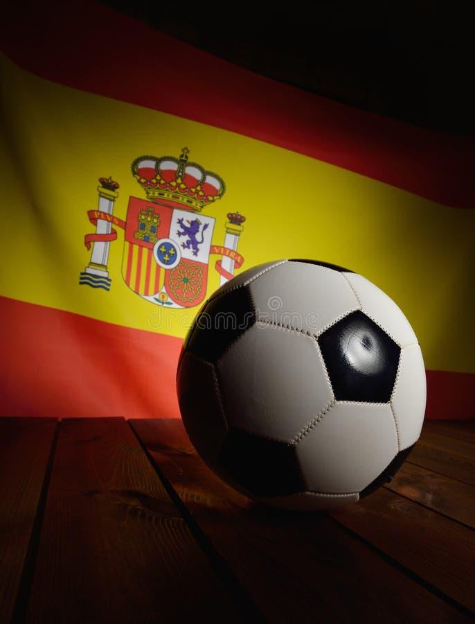Flagga av Spanien med fotboll på träbräden arkivfoton